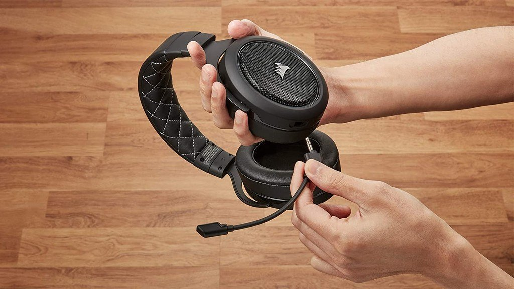 Someone plugging in the detachable microphone into a Corsair HS70 Pro, one of the best wireless gaming headsets for PC gamers on a budget.