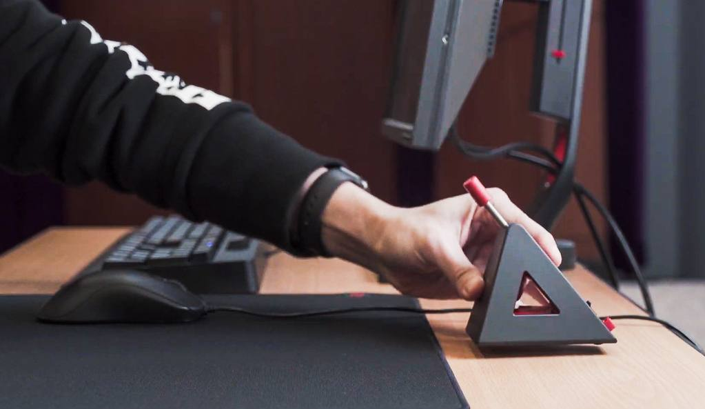 Side-view of a gamer setting up a gaming mouse bungee on their desktop.