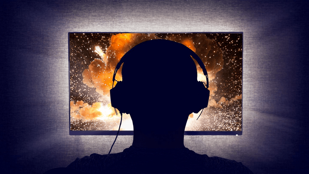 Photo of a silhouetted person sitting in front of a (gaming) monitor.