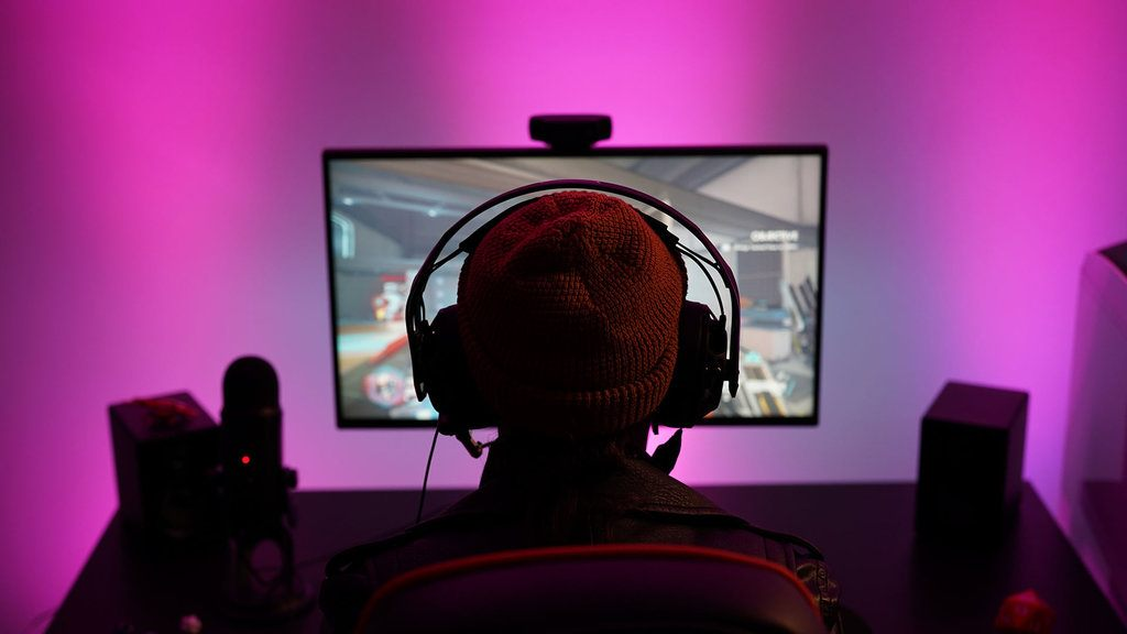 Photograph of a gamer in front of their display, experiencing virtual surround upscaling from Dolby Atmos.