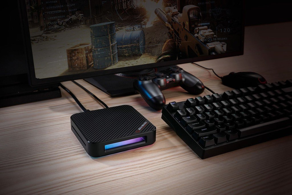 Picture of a gaming capture card on a desk, accompanied by other gaming peripherals.