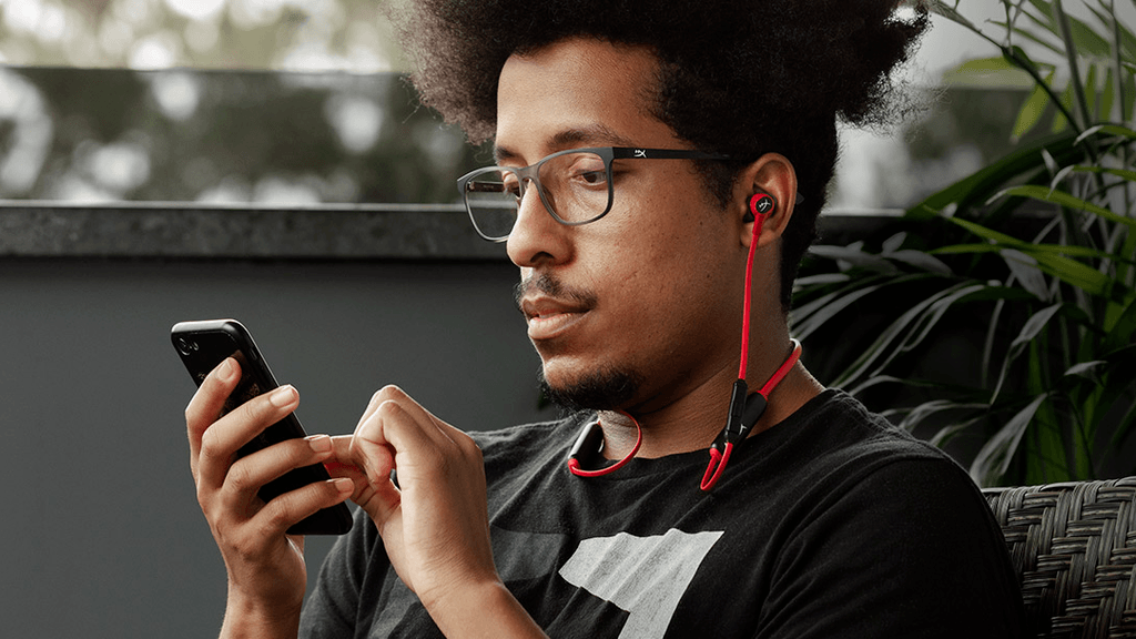 Photograph of a man using a smartphone with the HyperX Cloud Buds, a wireless set of gaming earbuds.
