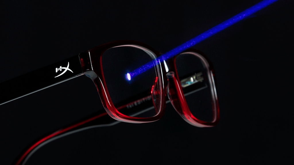 Image of a pair of gaming glasses from HyperX being tested by shining a blue laser on the lenses. The range of the laser is visibly blocked by the lenses.